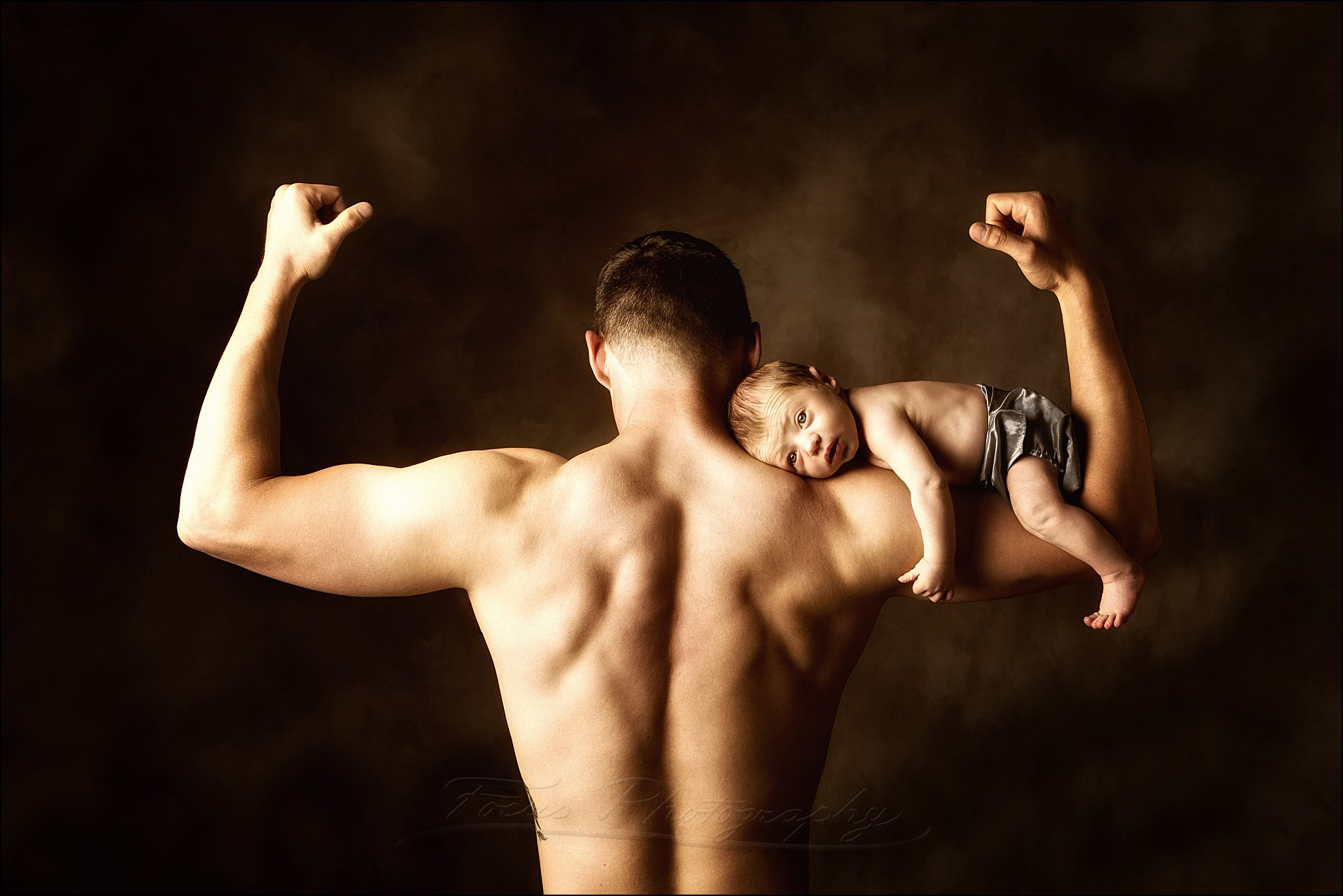 cute newborn pictures of father with baby balanced on his biceps