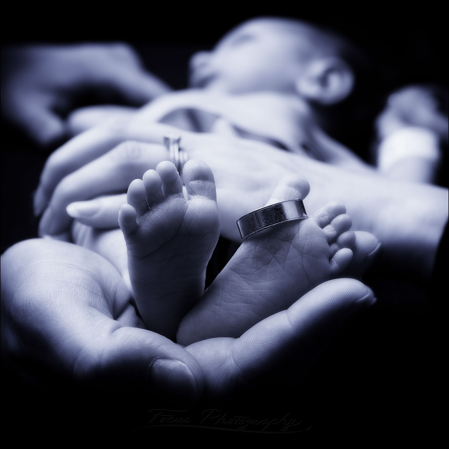 wedding ring on baby's feet in blue-toned image