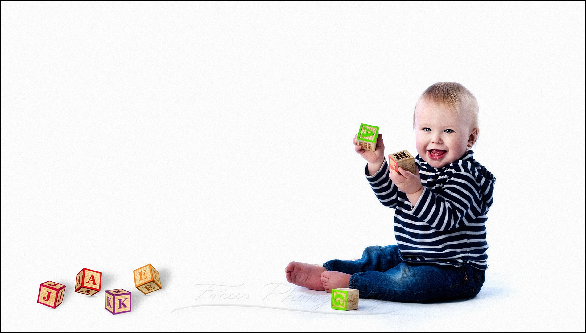 baby boy plays with blocks that spell out his name