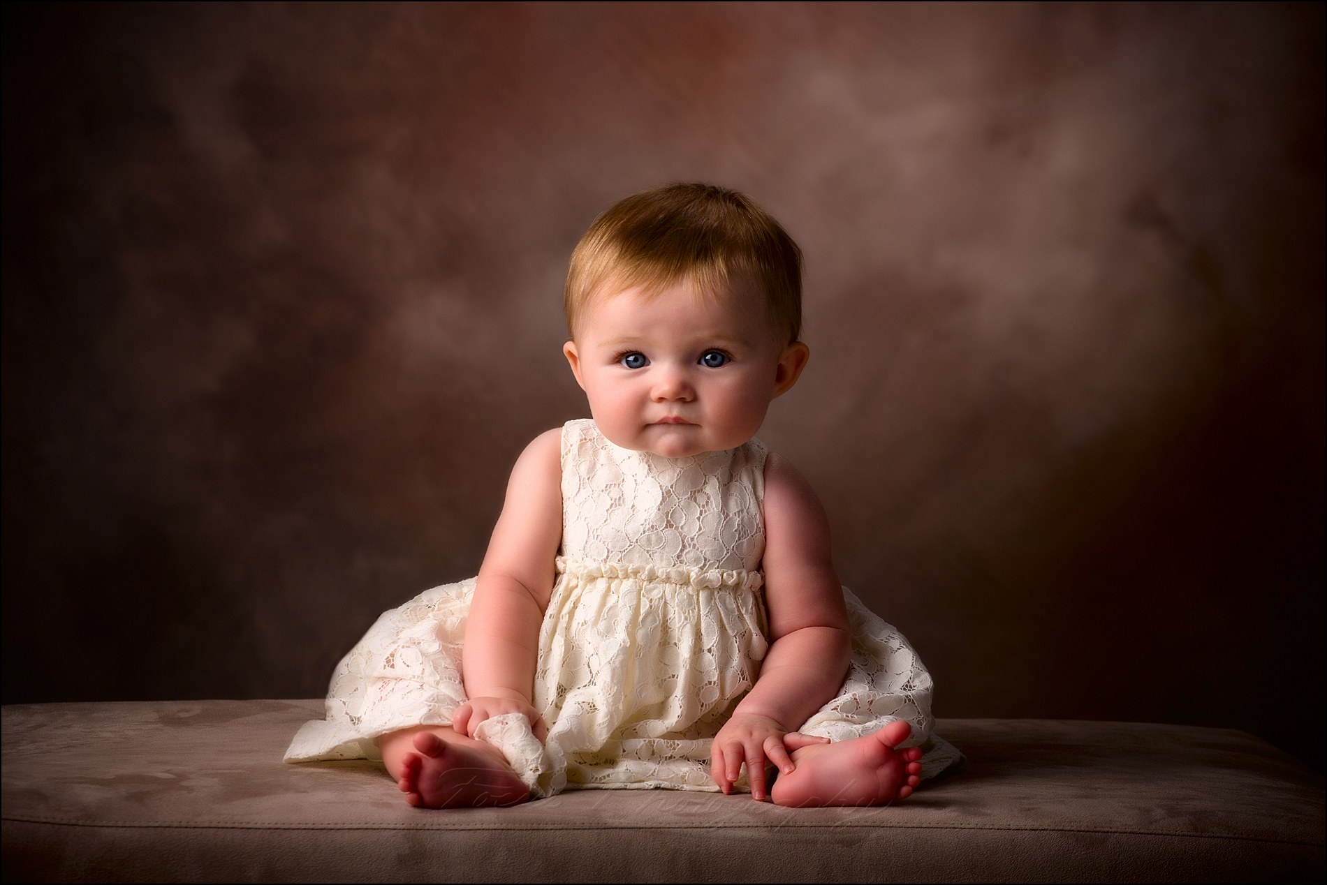 studio portrait photography of six month old baby sitting up on her own