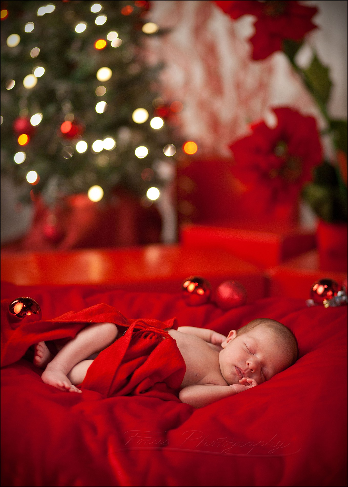 newborn baby girl in front of Christmas tree wrapped in ribbon