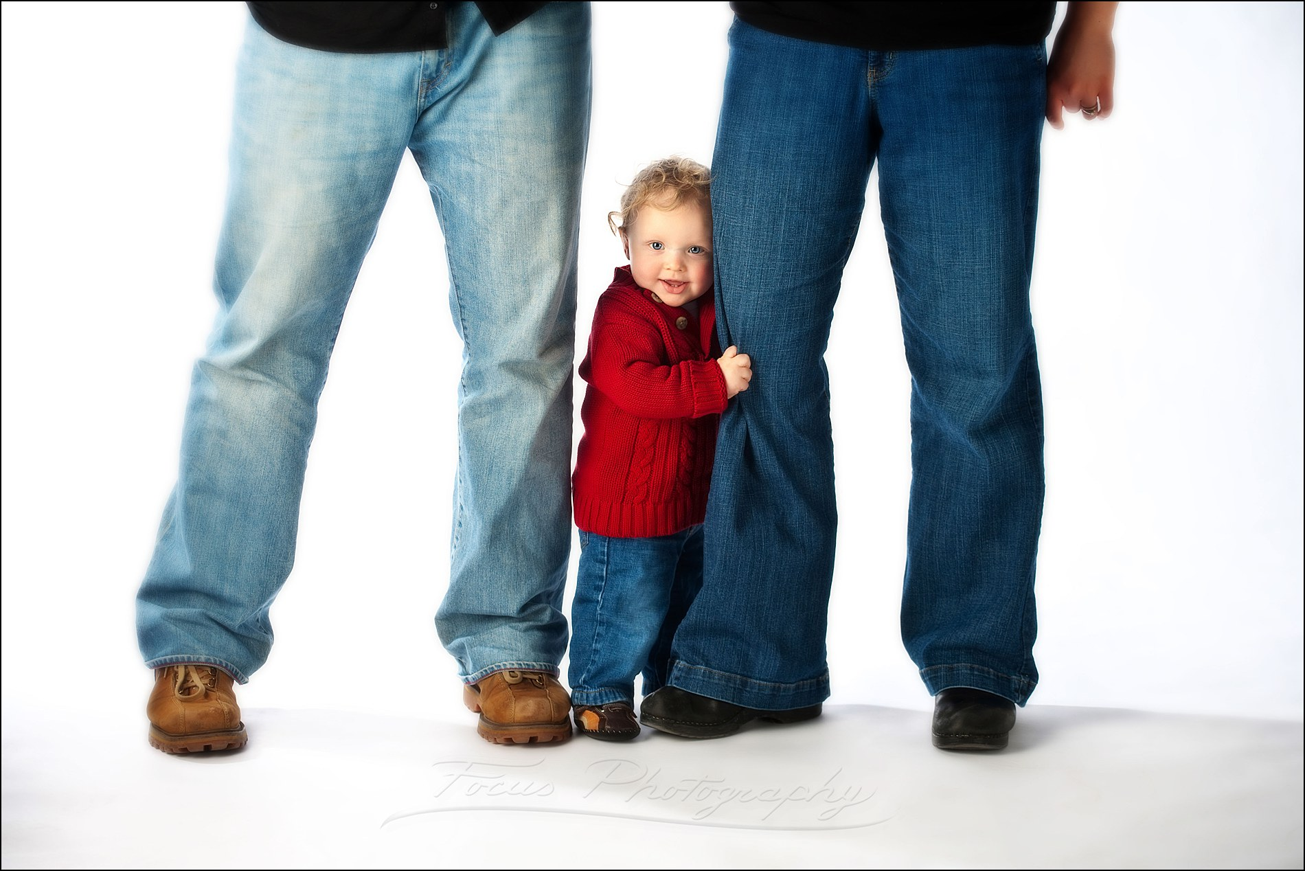 baby stands up supported by parents' legs in family picture