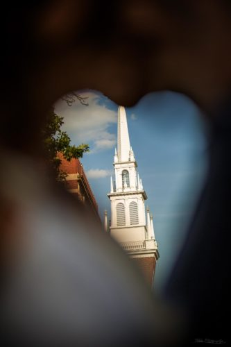 Here is the old north church framed by engaged couple kissing