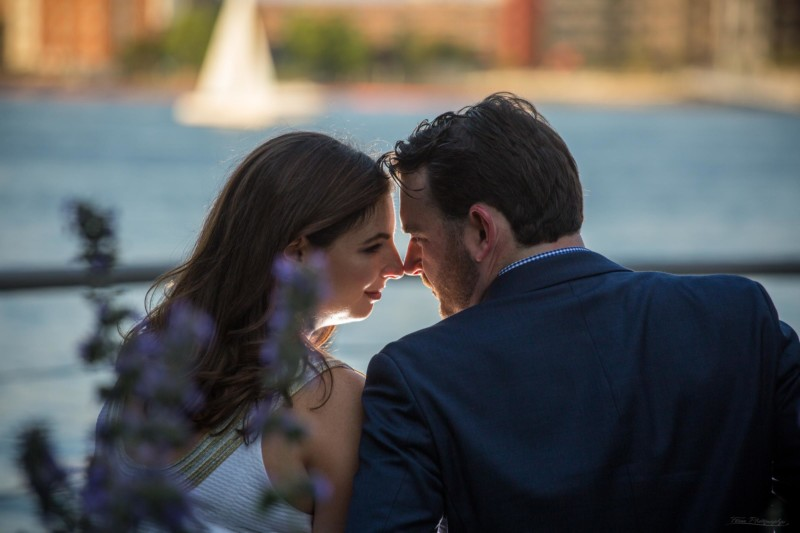 romantic engagement couple with noses together and sailboat in background