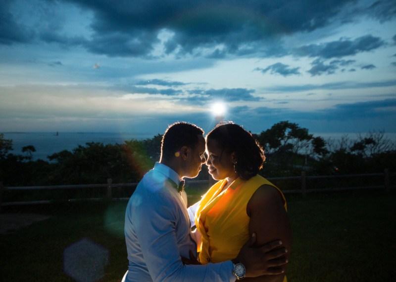 lighthouse beam backlights engaged couple during photoshoot