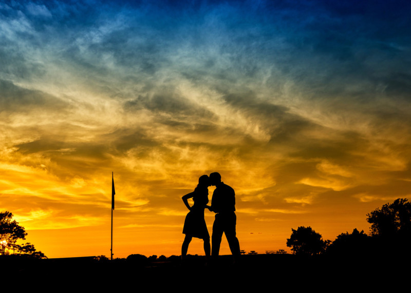 silhouette of engaged couple in front of sunset