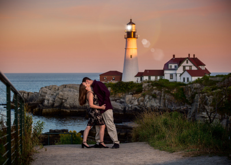 lighthouse shines behind engaged couple