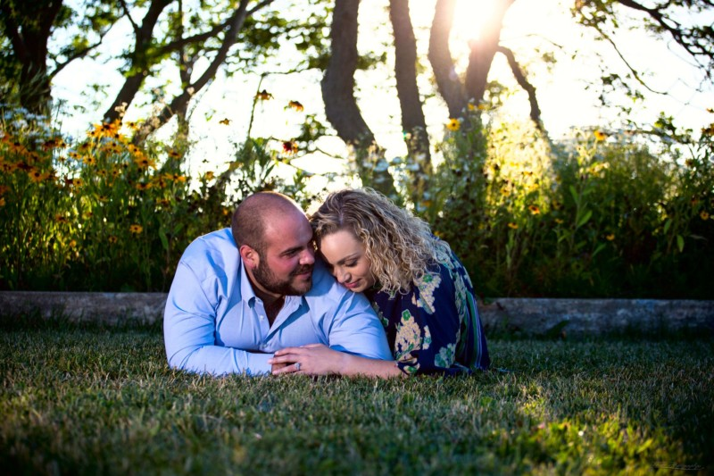 couple on grass for engagement pictures at Fort Williams Park in Cape Elizabeth
