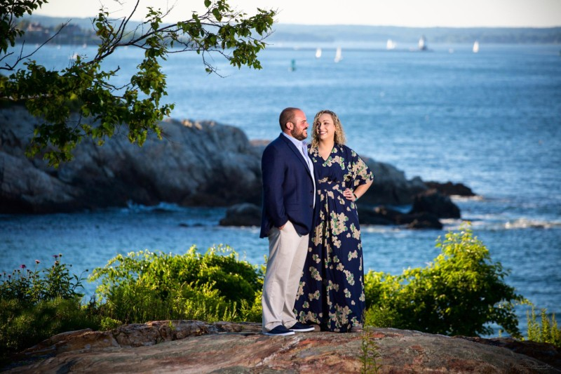 couple stands before casco bay for engagement pictures at Fort Williams Park