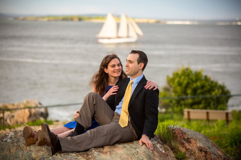wind jammer sails in casco bay behind engagement pictures at Fort Williams park