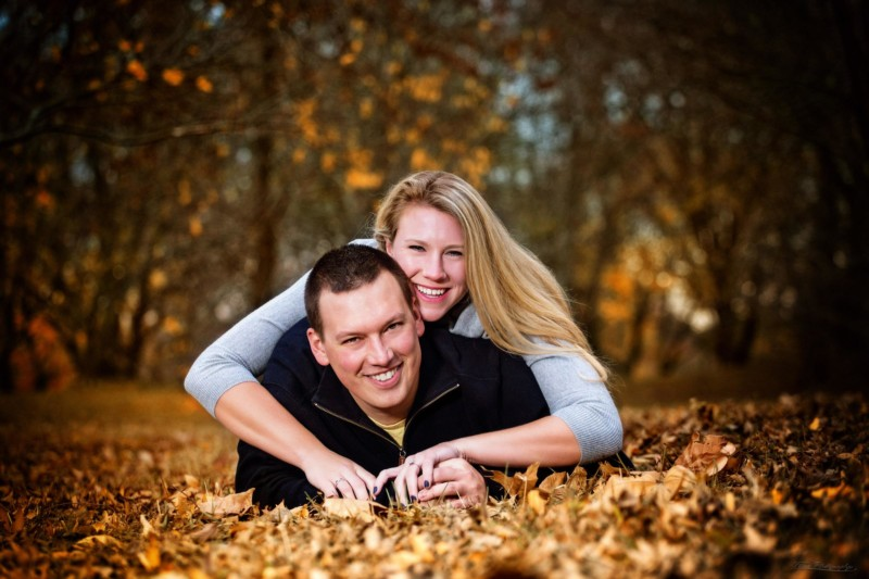 couple laying on leaves for engagement picture in boston, ma