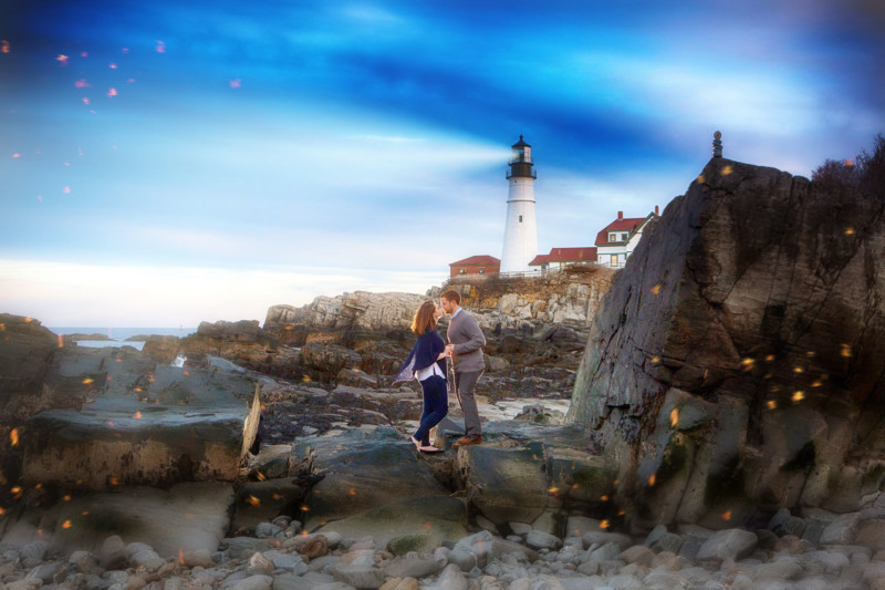 portland head light shines over engagement couple doing photoshoot