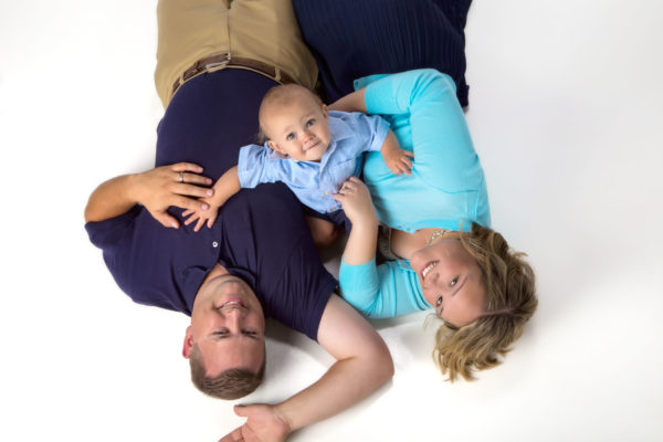 parents laying on floor and baby sitting up in contemporary family portrait in maine