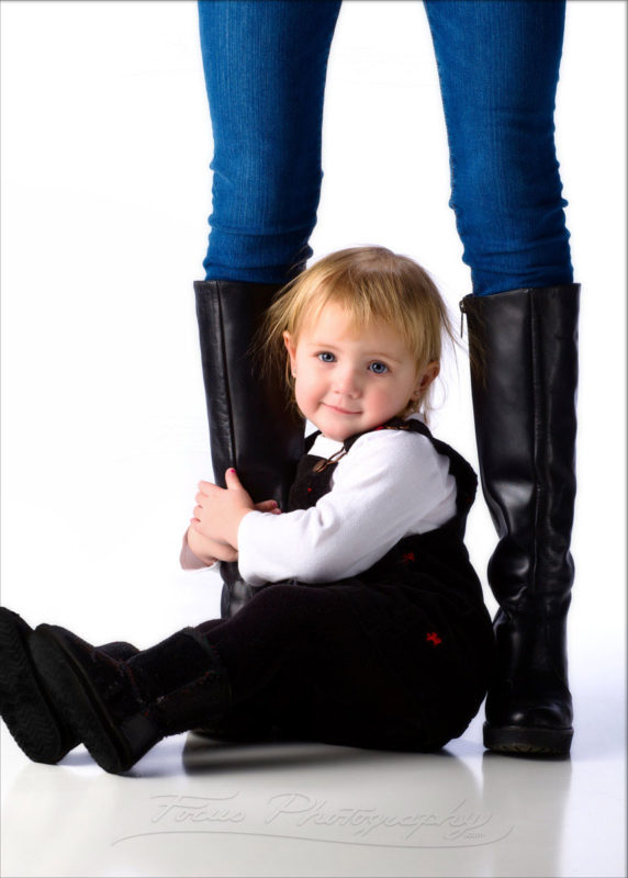 baby holds on to mom's boots for modern family photo