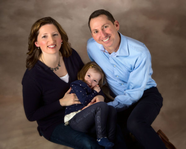 daughter curls up on mom in family picture in photography studio