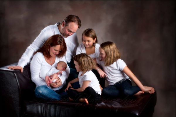 family watches their new baby in studio on brown background