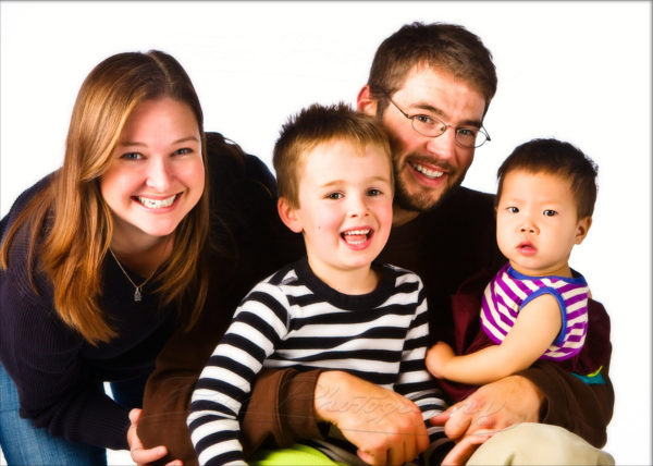 bright white background and fun striped shirts for modern family photo