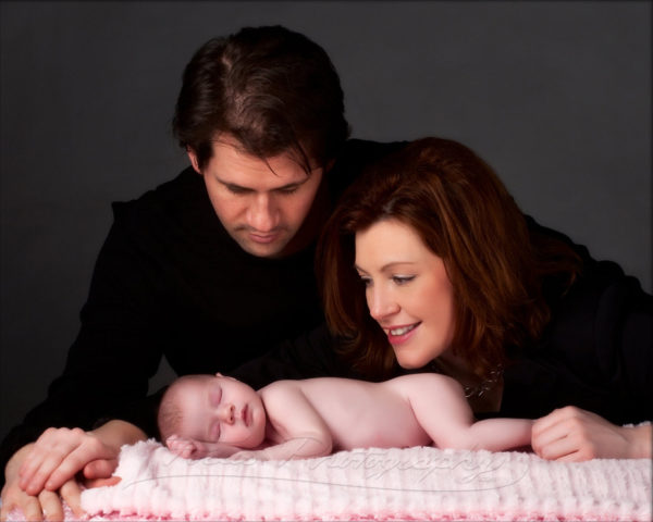 parents stare at baby girl in emotional family image