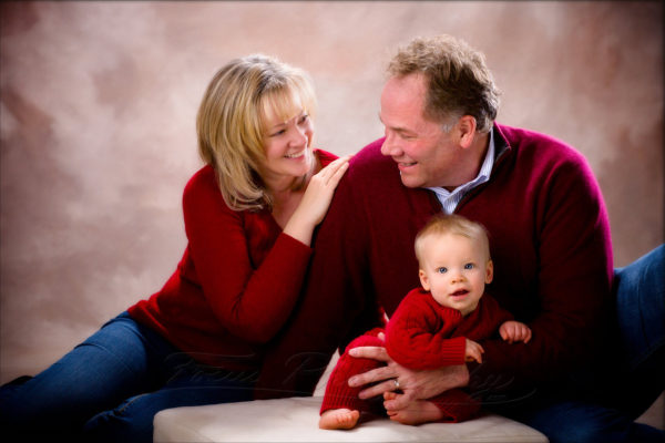 family photo in red sweaters on brown background
