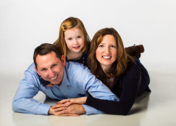 white high key photo of parents and young daughter for family portrait