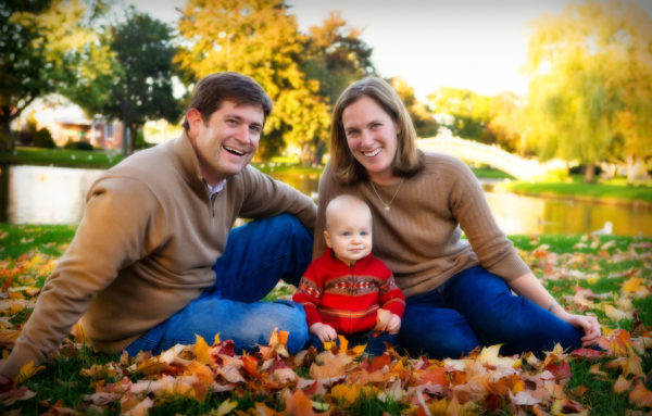 baby in fall sweater at park among leaves for family portrait