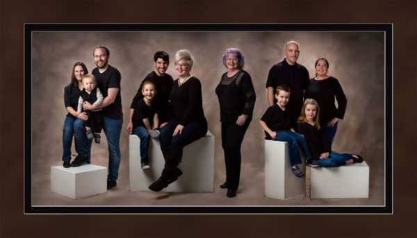 family wearing black and denim photographed in maine photography studio on brown background