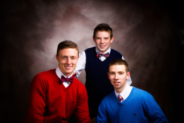 Three brothers photographed on brown background in photography studio.