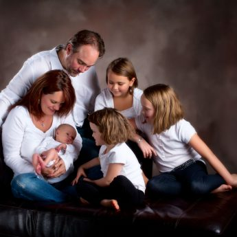 family portrait with new baby in photographers studio