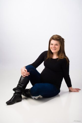 maternity picture seated on white in black shirt