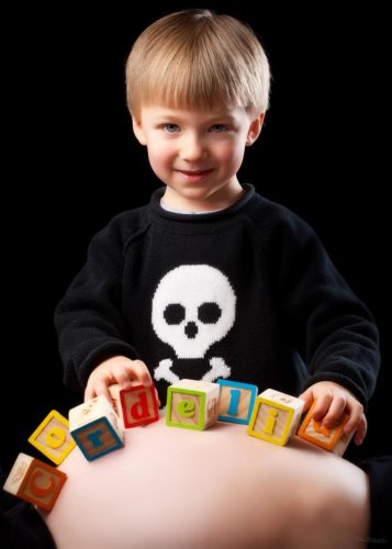 boy with baby blocks on pregnant belly