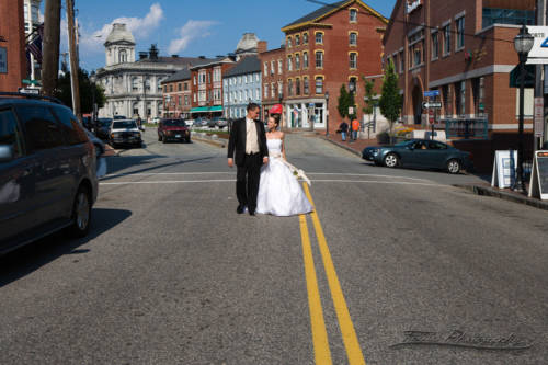 bride and groom walk down middle of fore street in portland, me