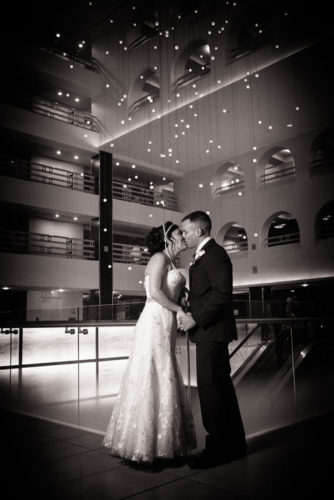 bride and groom kiss in atrium of the boston long wharf