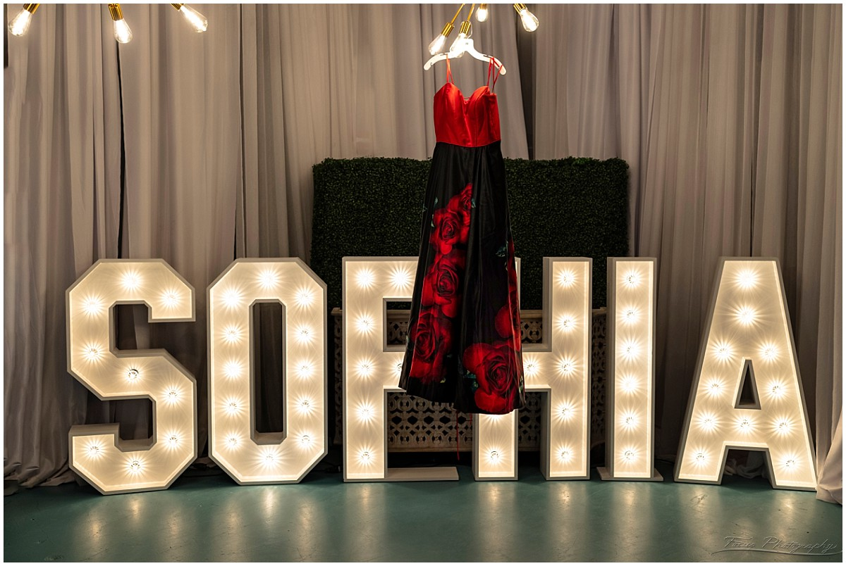 Quinceanera Party dress hanging in front of block letters
