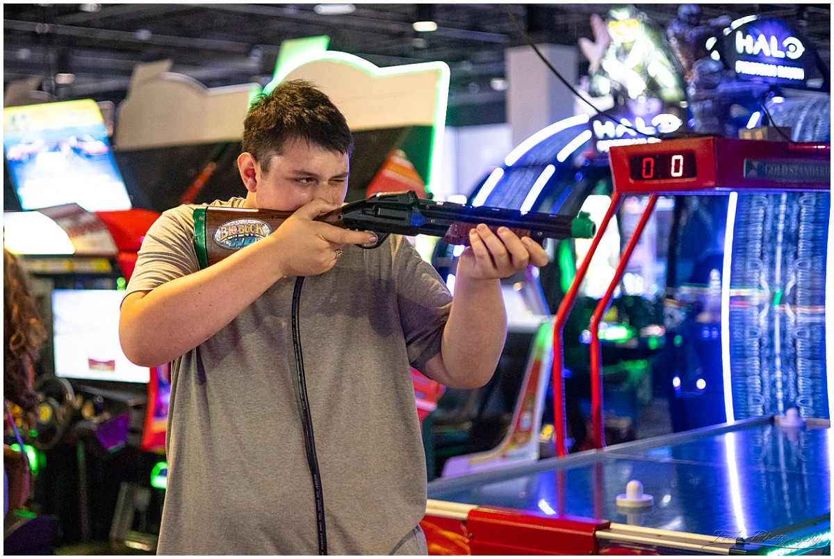 shooting guns in game at Round 1 arcade at Maine Mall