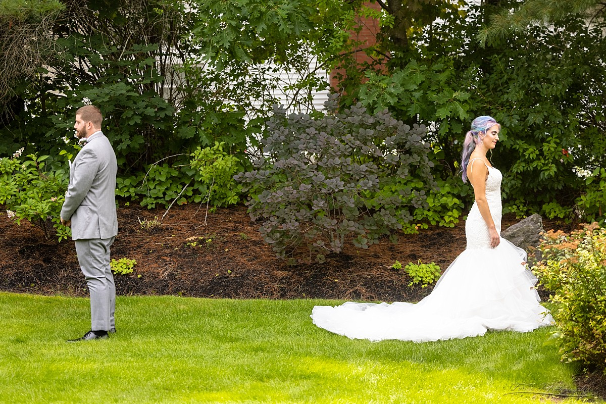 bride and groom stand back to back for dress reveal