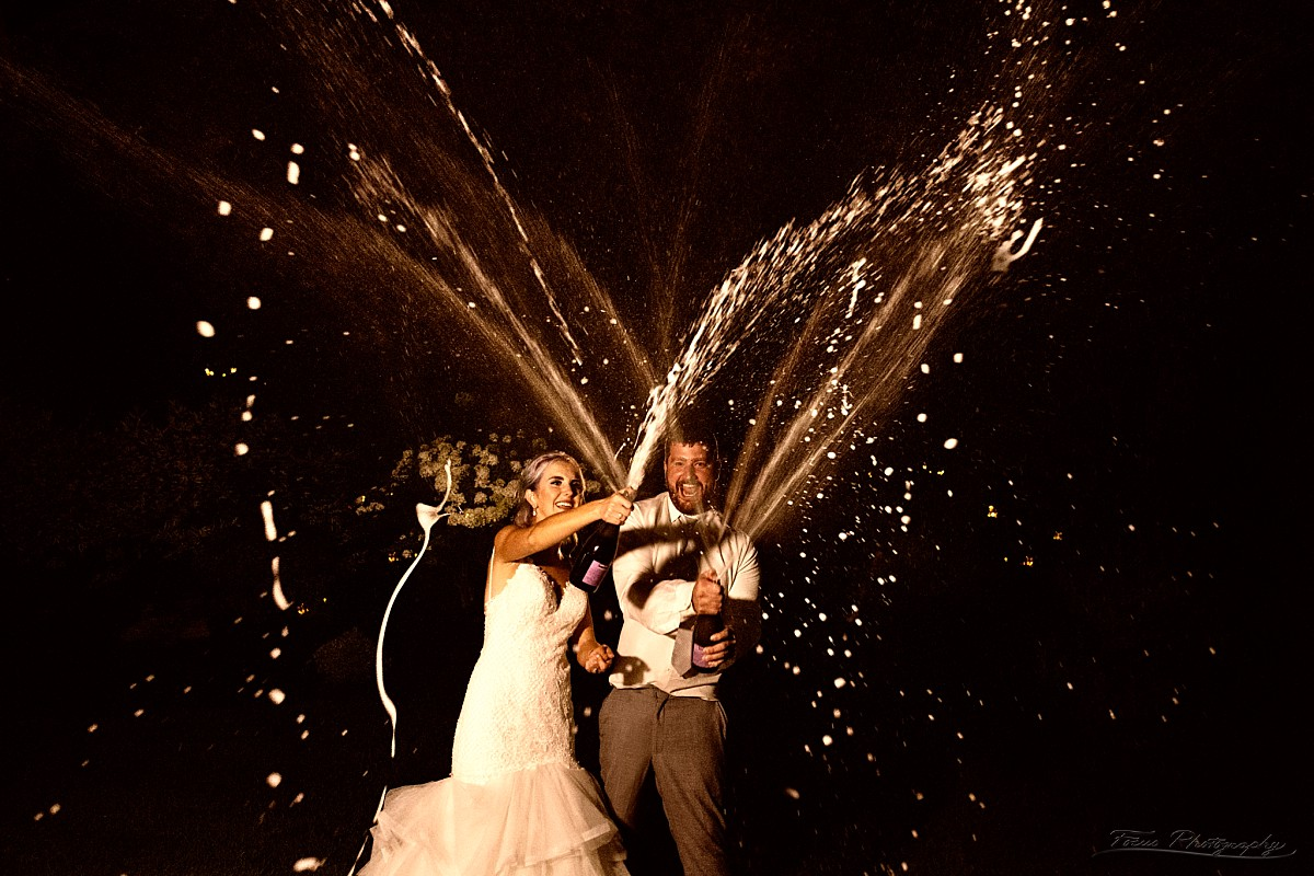 bride and groom spray champagne