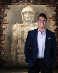senior portrait of guy in blue jacket standing in front of picture of him as quarterback for cool senior picture