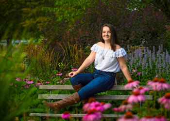 senior photographed on park bench among wild flowers in maine