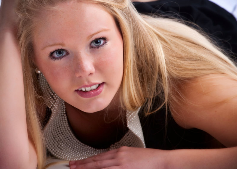 close up of senior girl photographed in professional photography studio laying on floor looking at camera