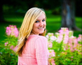girl with pink sweater photographed among pink flowers for senior pictures in Portland park