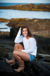 senior photo girl in boots on rocks above ocean on coast in maine
