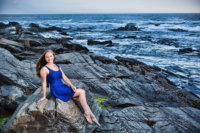 senior girl in blue dress photographed on rock by ocean by professional photographer
