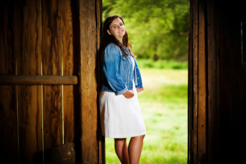 barn doors frame a high school senior girl at her house in this portrait