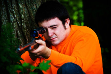 senior boy shows off hunting apparel in this portrait taken at his house