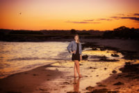 Kenzie was photographed at sunset for her senior pictures at the beach in Maine