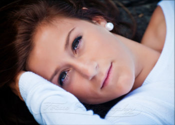senior photo of girl laying on ground in park