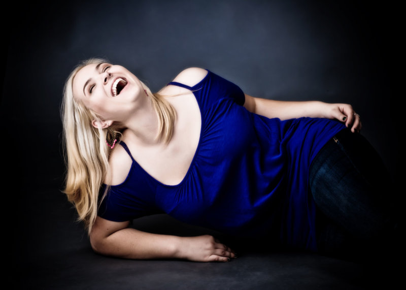 girl wearing blue top laughs while being photographed for senior portrait