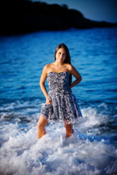 girl in dress has waves crash at feet in senior picture at beach in maine