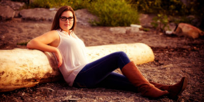 senior wearing boots and jeans sits at beach against driftwood for photos