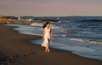girl in white dress walks along shore for senior pictures at beach